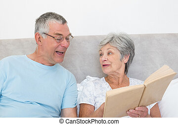 Senior woman showing book to husband in bed at home
