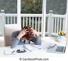 Senior woman showing depression while working on her financial matters