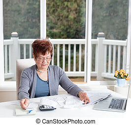 Senior woman showing frustration while working on her financial matters