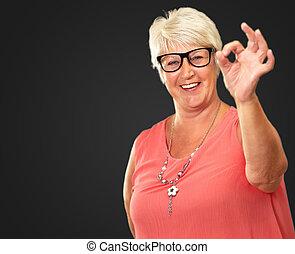 Senior Woman Showing Okay Sign Isolated On Black Background