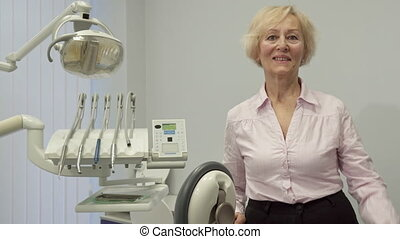 Senior woman shows her thumb up at the dentist office