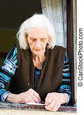 Senior woman signing retirement check at home