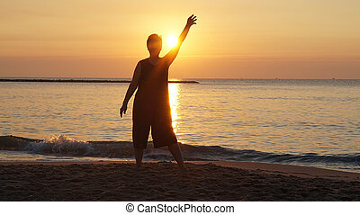 senior woman silhouette raising hand in front of new day ornage sunrise by the ocean