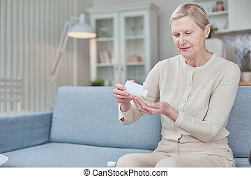 Senior woman sit on couch having daily vitamins or diet supplements at home, mature old female pensioner take dose of pills from meds bottle, elderly healthcare, medication concept