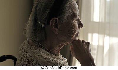 Senior woman sit on wheelchair and looks through the window