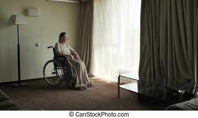 Senior woman sit on wheelchair and looks through the window