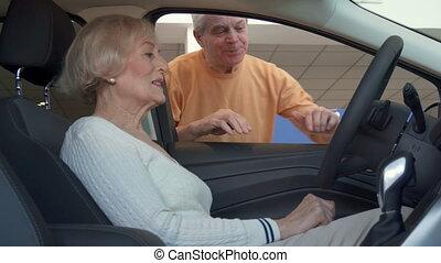 Senior woman sits inside the car