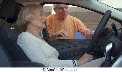 Senior woman sits inside the car