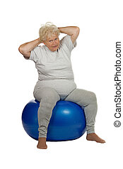 Senior woman sits on a fitball