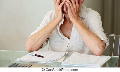 Senior woman sitting at table working out bills at home in...