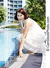 Senior woman sitting by pool