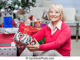 Senior Woman Sitting By Stack Of Christmas Presents