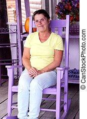 Senior woman sitting in purple rocking chair smiling