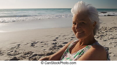 Senior woman sitting looking away at the beach - Portrait of...