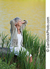 Senior woman sitting near a lake for fresh breathe - A...