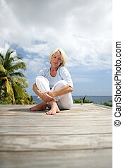 Senior woman sitting on a deck