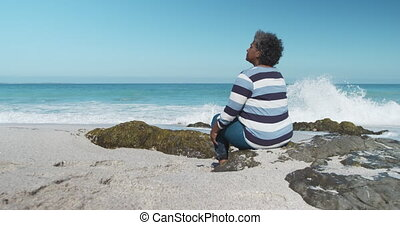 Senior woman sitting on a rock at the beach