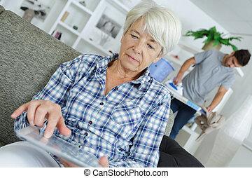 senior woman sitting on a sofa near male carer