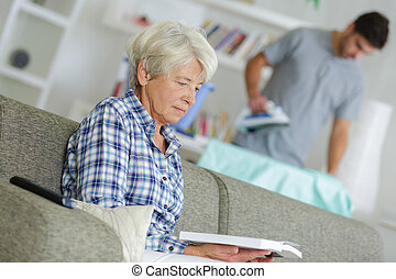 senior woman sitting on a sofa with a book