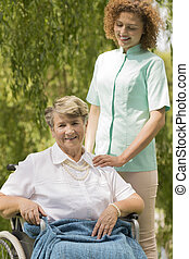 Senior woman sitting on a wheelchair and nurse - Senior...