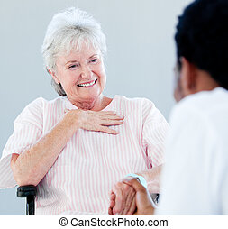 Senior woman sitting on a wheelchair talking with her doctor