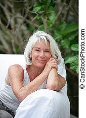 Senior woman sitting on an outdoor sofa