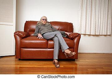 Senior woman sitting on leather sofa