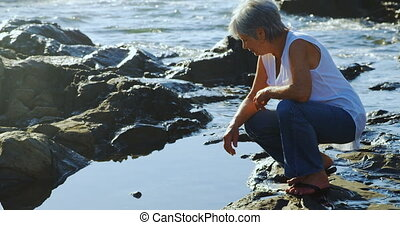 Senior woman sitting on rock near side 4k - Senior woman...