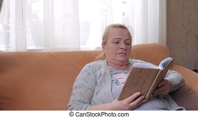 Senior woman sitting on sofa and reading a book