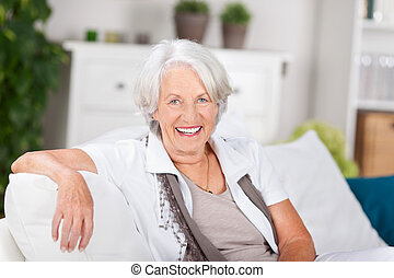 Senior Woman Sitting On Sofa At Home