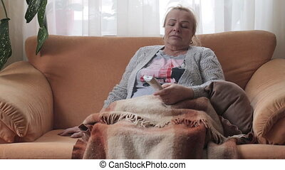 Senior woman sitting on sofa holding the remote. Elderly woman watch TV