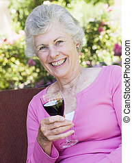 Senior woman sitting outdoors on a chair with a glass of red wine