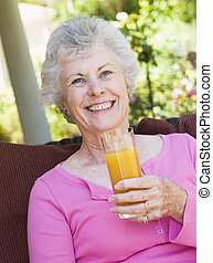 Senior woman sitting outdoors with a glass of orange juice