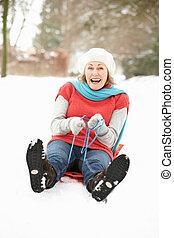 Senior Woman Sledging Through Snowy Woodland
