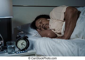 senior woman sleeping in bed at night