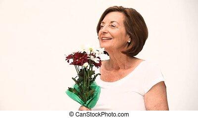 Senior woman smelling a flower