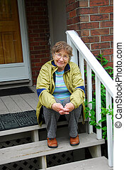 Senior woman smiling - Senior woman sitting on a porch