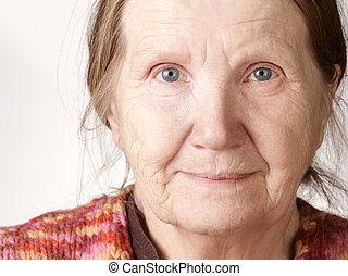 senior woman smiling to camera, close up portrait