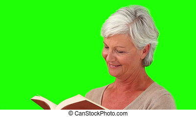 Senior woman smiling while reading a book