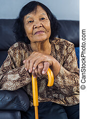 senior woman smiling with wooden cane