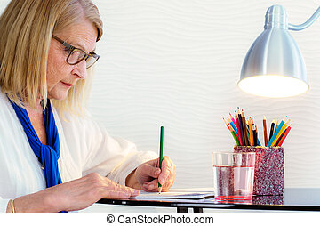 Senior woman spending time with coloring book.