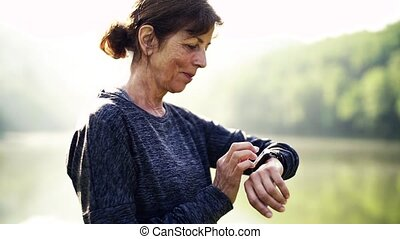 Senior woman standing by the lake outdoor in foggy morning...