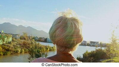 Senior woman standing in backyard 4k
