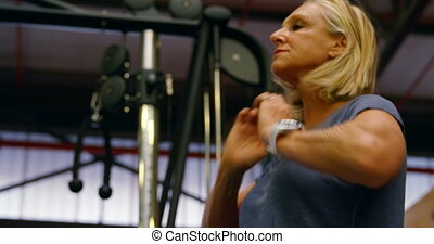 Senior woman standing in fitness studio 4k - Close-up of...