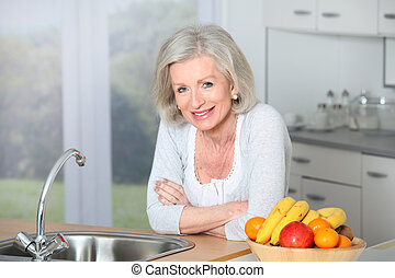 Senior woman standing in kitchen