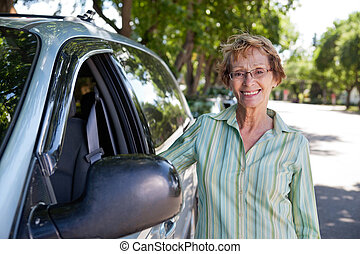 Senior woman standing near car - Portrait of beautiful ...