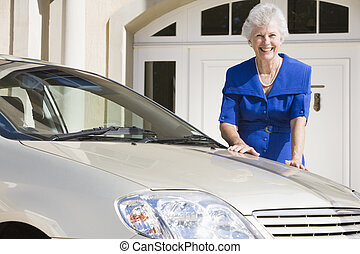 Senior woman standing next to new car