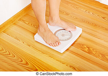 Senior woman standing on weight scale in living room