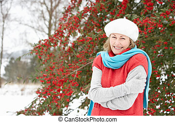 Senior Woman Standing Outside In Snowy Landscape
