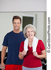 Senior Woman Standing With Male Instructor In Gym